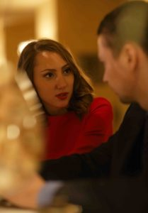 Young woman in red dress and man with a glass of wine talking in the cafe or restaurant