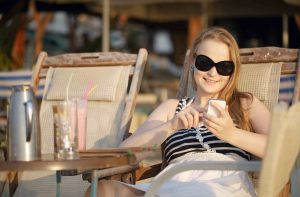 Attractive woman wearing sunglasses relaxing in a deckchair in the sun sending an sms on her mobile phone