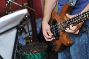 young music player and band friends have training in home garage