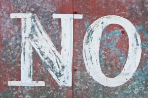 vintage word NO on a rusty red metallic surface