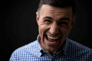 Portrait of a man screaming over black background and looking at camera